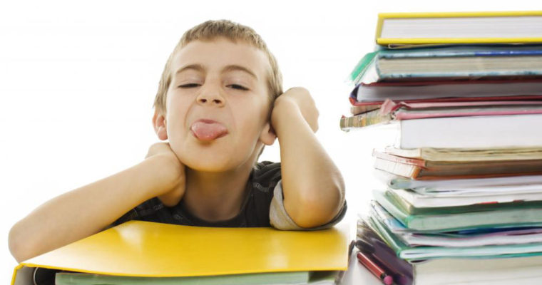 boy-sticking-out-tounge-with-stacks-of-books